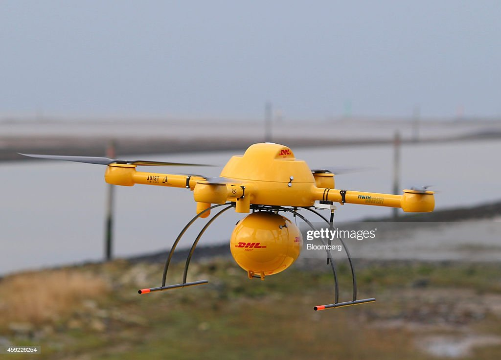 The DHL logo sits on a parcel delivery drone, manufactured by Microdrones GmbH, as it takes off during testing by Deutsche Post AG's parcel delivery unit on the North Sea coast in Norddeich, Germany, on Tuesday, Nov. 18, 2014. The trial-run may help Deutsche Post stake a claim to a part of the logistics chain in which postal operators and express service providers are increasingly being challenged by Internet retailers. Photographer: Jasper Juinen/Bloomberg via Getty Images