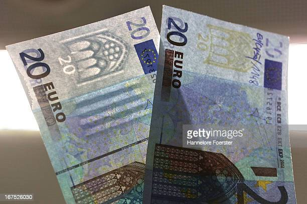 The difference between a real and a fake 20 Euro note at the counterfeit money analysis lab of the German Bundesbank during a demonstration for the...