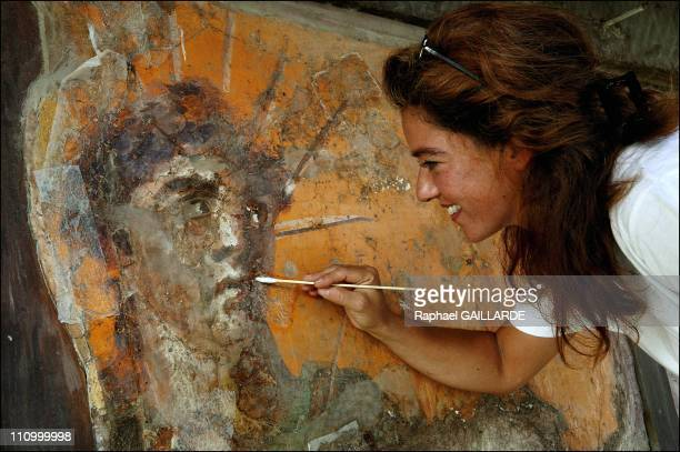 The difficult task of preserving Pompeii a race against decay Facade of the felt makers' shop in Via dell'Abbondanza in Pompeii A restorer face to...