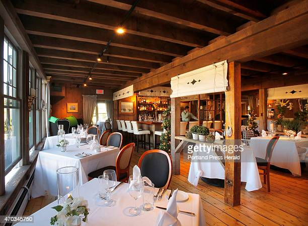 The dining areas of On the Marsh Bistro in Kennebunk are decorated with upholstered furniture ornate wooden chandeliers patterened pillows and oil...