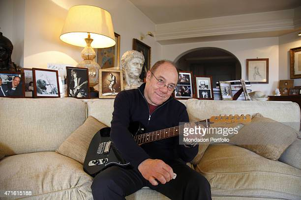 'The director and actor Carlo Verdone playing his new Fender guitar at home for a photo shooting Behind him the pictures of his favourite rockstars...