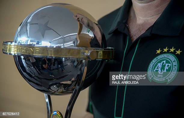 The director of Brazil's Chapecoense football club Marcelo Zolet holds a replica of a Copa Sudamericana trophy sent by the president of Colombia's...