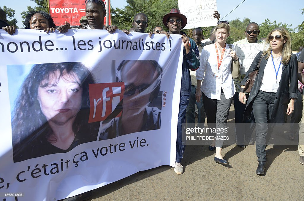 The director of France Medias Monde, Marie-Christine Saragosse (R), and the director of Radio France Internationale (RFI) Cecile Megie (2ndR), attend a white march with Malian journalists on November 4, 2013 in Bamako, in memory of Radio France Internationale (RFI) journalist Ghislaine Dupont (L) and sound technician Claude Verlon (R) killed in the town of Kidal. French troops were working today with Malian security forces to hunt the killers of the two French journalists shot dead in the west African nation's rebel-infested northern desert. Ghislaine Dupont, 57, and Claude Verlon, 55, were kidnapped and killed by what French Foreign Minister Laurent Fabius said were 'terrorist groups' in the flashpoint northeastern town of Kidal on November 2, 2013. AFP PHOTO / PHILIPPE DESMAZES