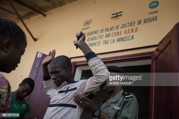 The director of the Bouar detention center performs a body check on people who enter Bouar's High Court in Bouar western Central African Republic on...