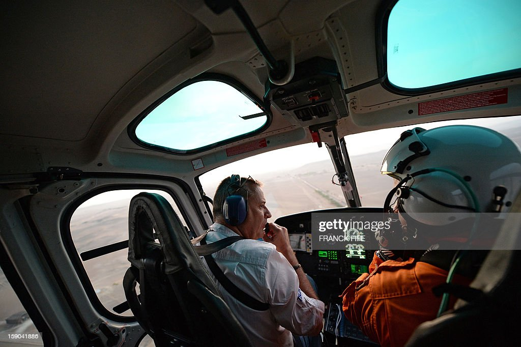 The director of the Dakar Rally 2013 Etienne Lavigne (L) remains on his helicopter during the Stage 2 of the Dakar 2013 in Pisco, Peru, on January 6, 2013. The rally will take place in Peru, Argentina and Chile from January 5 to 20.