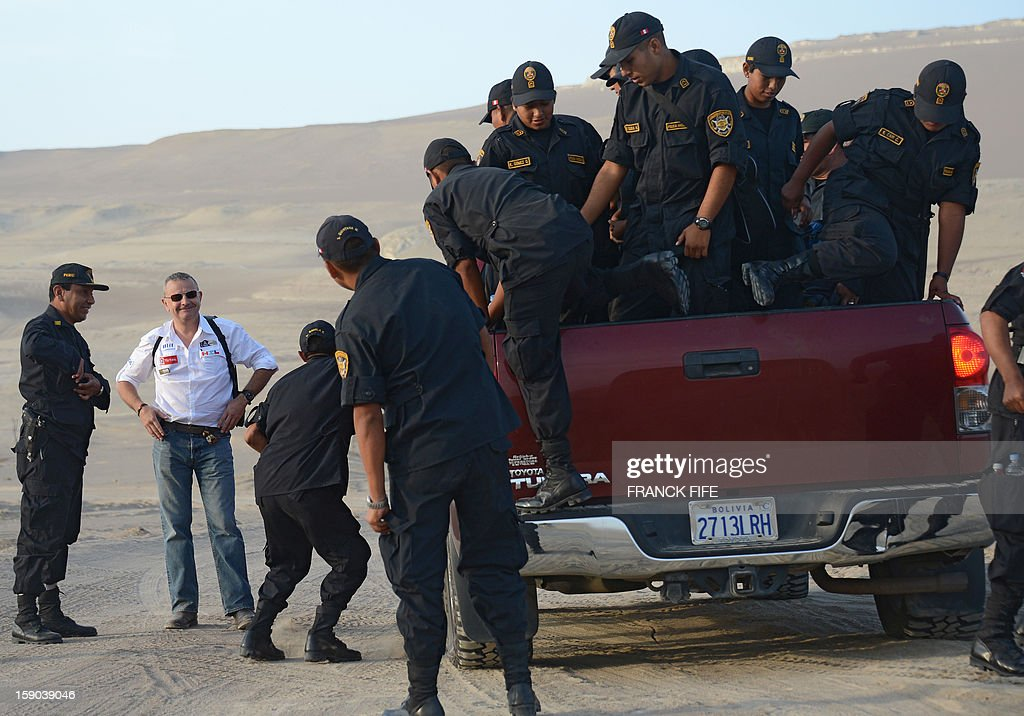 The director of the Dakar Rally 2013 Etienne Lavigne (2-L) speaks with policemen before the start of the Stage 2 of the Dakar 2013 in Pisco, Peru, on January 6, 2013. The rally will take place in Peru, Argentina and Chile from January 5 to 20.