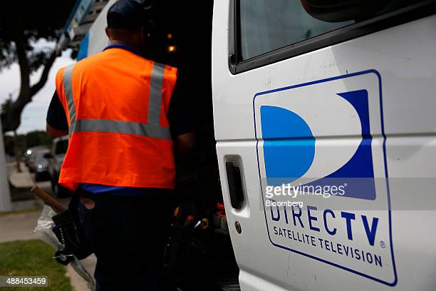 The DirecTV logo is seen as a technician stores equipment in a service truck after installing a new satellite TV dish at an apartment building in...