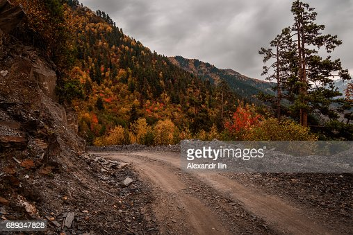 The dirt road strewn with rocks on the background of Georgian forested mountains. : Stock Photo