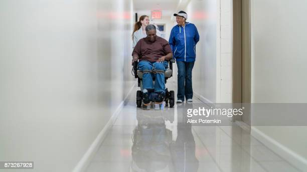 The disabled African-American man in wheelchair, accompanied with Black woman and White teenager girl, in the corridor of the residential living building in Bronx