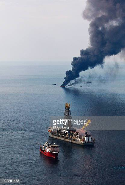 The Discoverer Enterprise drillship leased by BP Plc burns off gas carried up with oil it collects as smoke rises from controlled burns of oil on the...