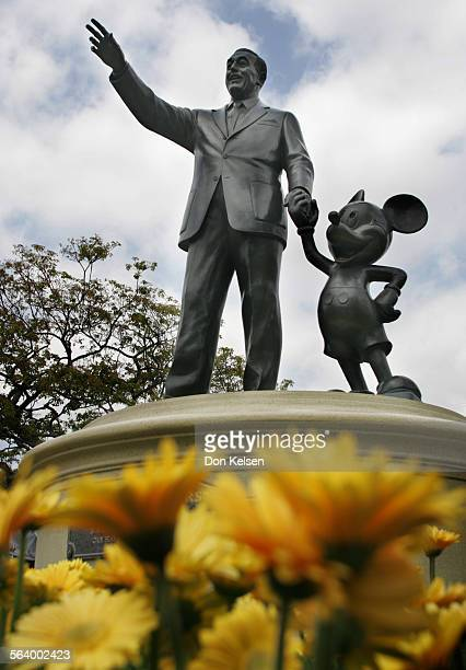 The Disneyland 'Partners Statue' surrounded by golden flowers located on Disneyland's Main Street USA near Sleeping Beauty's Castle Disney borrowed...
