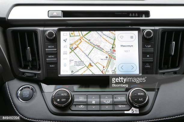 The display screen of an integrated YandexAuto incar connected service system showing a road navigation map sits on the dashboard of a Toyota Motor...