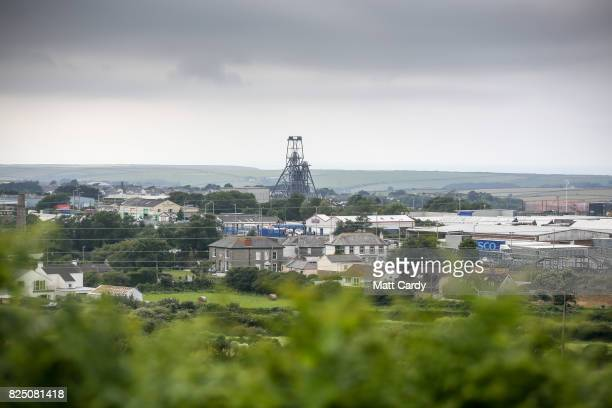 The disused mine shaft headgear and pulley wheel of the South Crofty mine is seen over the surrounding town of Camborne on July 24 2017 in Cornwall...