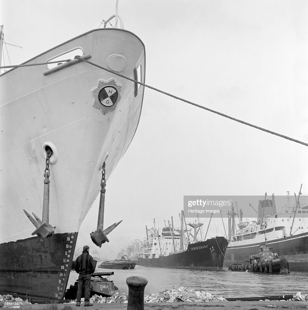 The Docks London July 1965 A man standing in front of a moored ship with massive anchors overhead and a tug towing the ship 'Tewkesbury' to the right