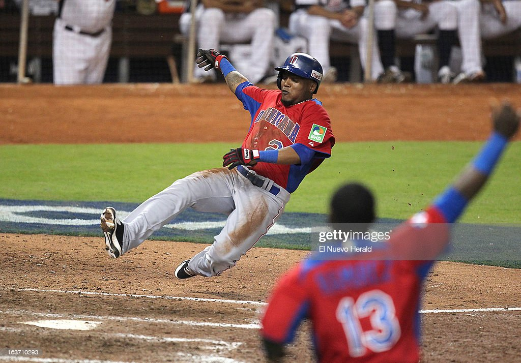 The Dominican Republic's Erick Aybar slides safely at home plate after an RBI single by Jose Reyes during the ninth inning against the United States at Marlins Park in Miami, Florida, on Thursday, March 14, 2013. The Dominican Republic won, 3-1.