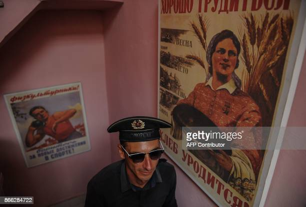 The doorman of the retroSoviet restaurant Nazdarovie Dimitri Fidel walks up the stairs of the restaurant in Havana on October 16 2017 With three...