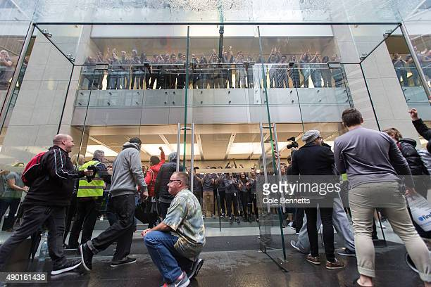 The doors open as crowds wait in anticipation for the release of the iPhone 6s and 6s Plus at Apple Store on September 25 2015 in Sydney Australia...