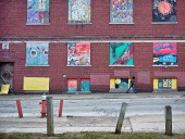 The drab plywood covering the windows of this vacant and condemned community center have been painted over with more colorful scenes on February 2...