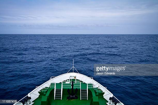 The bow of a ship heading towards a vast and distant ocean horizon.