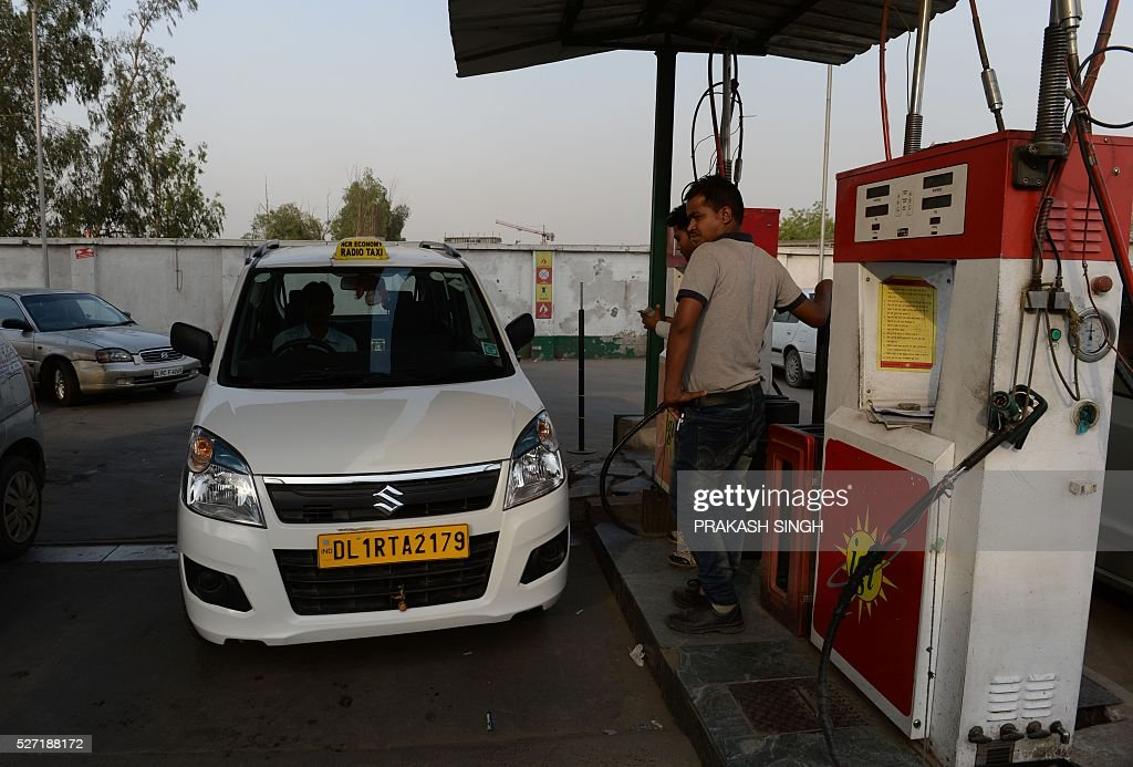 The driver of a compressed natural gas (CNG)-run taxi car waits to get his vehicle filled with CNG at a station in New Delhi on May 2, 2016. Hundreds of taxi drivers took to the streets of New Delhi to protest a court order banning diesel cabs from plying the roads of the world's most polluted capital. The ban would impact some 27,000 diesel taxis registered in Delhi, including app-based cab operators Ola and Uber. / AFP / PRAKASH