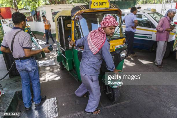 The driver of an auto rickshaw pulls his vehicle before refueling it with compressed natural gas at an Indraprastha Gas Ltd gas station in New Delhi...