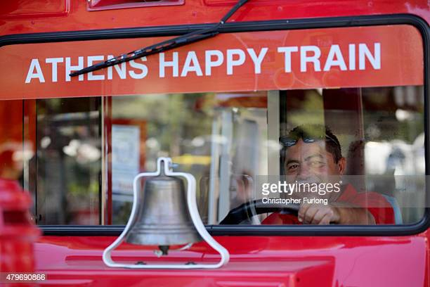 The driver of the Athens Happy Train smiles for tourists on July 6 2015 in Athens Greece Politicians in Europe and Greece are planning emergency...