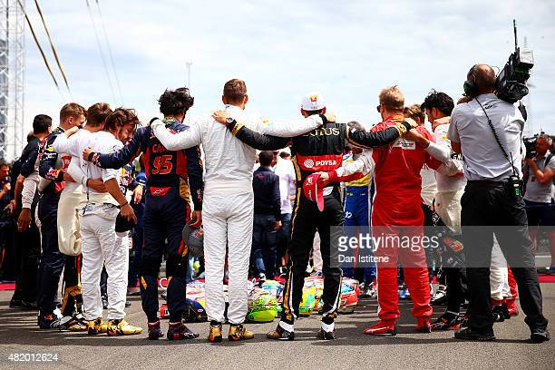 The drivers prepare to form a huddle around their helmets including Jules Bianchi's with the late driver's family on the grid before the Formula One...