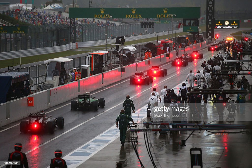 The drivers pull into the pit lane after the race is stopped permanently under a red flag during the Japanese Formula One Grand Prix at Suzuka...