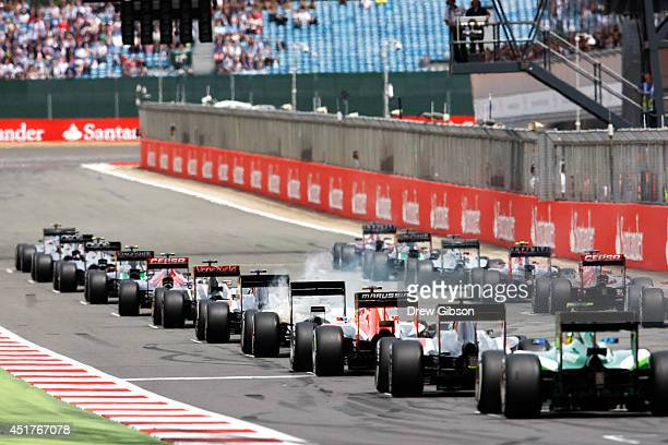 The drivers start the race behind the safety car during the British Formula One Grand Prix at Silverstone Circuit on July 6 2014 in Northampton...