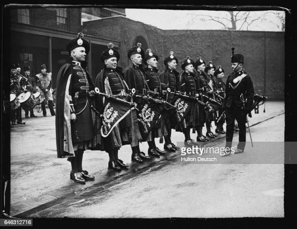 The Drum Major wearing the London Irish Rifles full dress uniform inspects the pipers who are wearing the Coronation Caubeen at the Duke of York's...