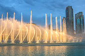 Night view of the light show at Dubai Dancing Fountain. The Dubai Fountain, the world largest choreographed fountain on Burj Khalifa Lake area, performs to the beat of the selected music.