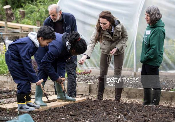 The Duchess of Cambridge helps children from Vauxhall primary school in London plant onions in their vegetable patch during a visit to a 'Farms for...