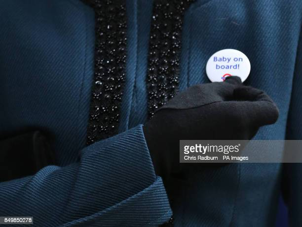 The Duchess of Cambridge holds a badge that reads Baby on Board given to her during a visit to Baker Street Tube Station in London to mark 150th...