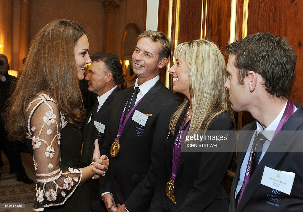 The Duchess of Cambridge smiles as she talks to (left to right) Carl Hester, Charlotte Dujardin, and Scott Brash during a reception for Team GB Medallists at the 2012 London Olympic and Paralympic Games at Buckingham Palace in London on October 23, 2012.