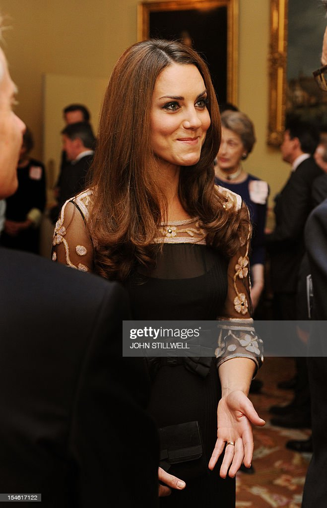 The Duchess of Cambridge smiles as she talks to Olympic and Paralympic athletes during a reception for Team GB Medallists at the 2012 London Olympic and Paralympic Games at Buckingham Palace in London on October 23, 2012. AFP PHOTO / POOL / JOHN STILLWELL