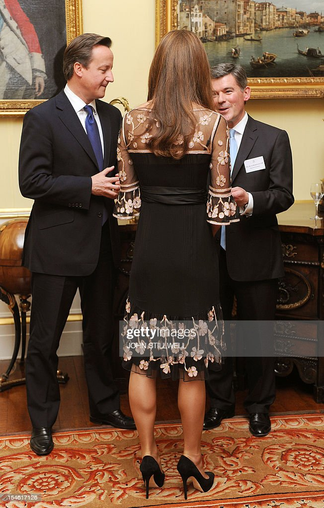 The Duchess of Cambridge talks to Prime Minsister David Cameron (L) and Sports Minister Hugh Robertson during a reception for Team GB Medallists at the 2012 London Olympic and Paralympic Games at Buckingham Palace in London on October 23, 2012.