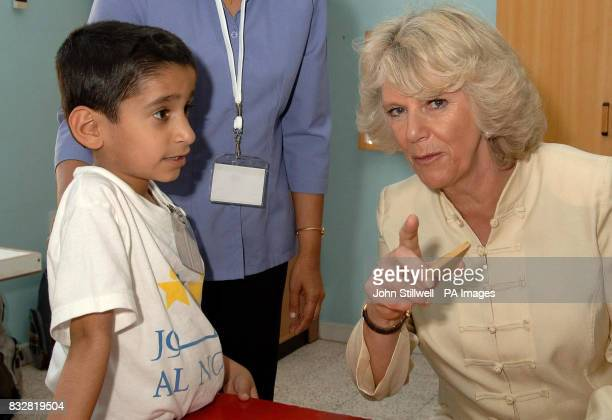 The Duchess of Cornwall asks Ibrahim Shezada aged 6 to smile for the camera during her visit to a special needs school in Dubai this morning