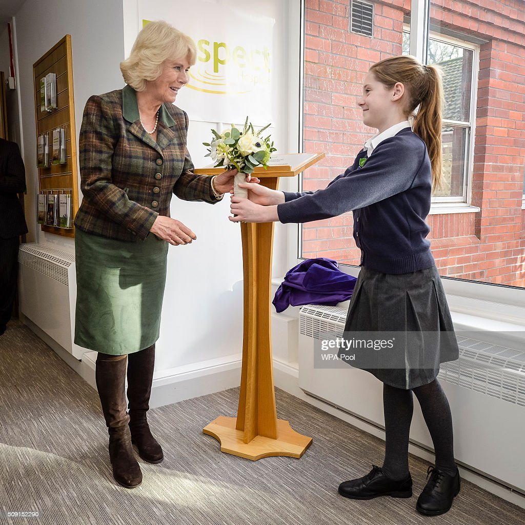 The Duchess of Cornwall is presented a posie by Burbage Primary School pupil Elizabeth Renshaw during a visit to Prospect Hospice's new facility at Savernake Hospital which gives care and support to patients, carers and families dealing with terminal illness on February 9, 2016 in Marlborough, England.