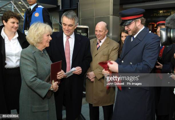 The Duchess of Cornwall is presented with some Harry Potter souvenirs from the shop close to the Hogwarts Express fictional Platform of 9 and three...