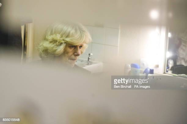 The Duchess of Cornwall is reflected in a mirror in a dressing room during a visit to the Theatre Royal in Bath