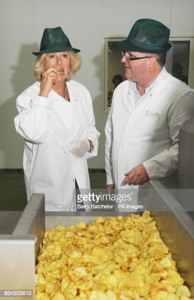 The Duchess of Cornwall is watched by Managing Director Les Sayers as she tastes a potato chip during her tour of Tyrrells Potato Chip factory near...