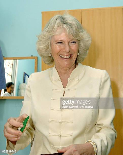 The Duchess of Cornwall laughs after Ibrahim Shezada aged 6 pokes his tongue out at the media during her visit to a special needs school in Dubai...