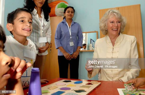 The Duchess of Cornwall laughs as Ibrahim Shezada aged 6 pokes his tongue out at the media during her visit to a special needs school in Dubai this...
