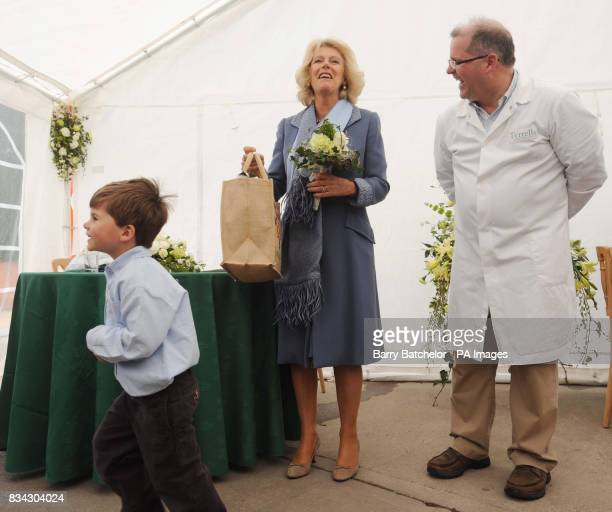 The Duchess of Cornwall laughs with Managing Director Les Sayers as she is given a 'goodie' bag of products by Henry Holloman at the end of her visit...