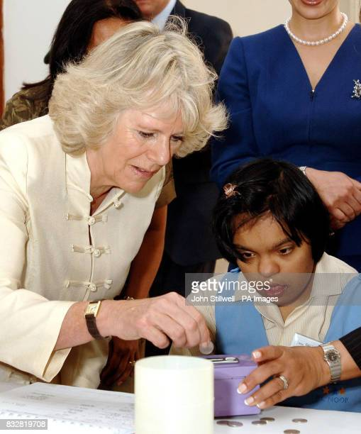The Duchess of Cornwall makes a contribution to the money box of a young girl during her visit to a special needs school in Dubai this morning