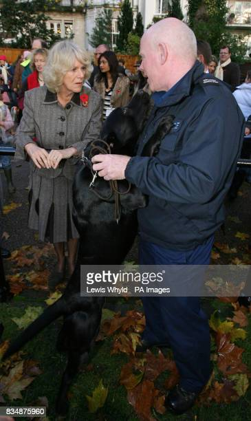 The Duchess of Cornwall meets a police dog and handler during a charity celebration of the Nepalese 'Day of the Dog' in the garden of the Royal...