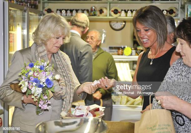 The Duchess of Cornwall pays for a jar of Lazerton honey with a ten pound note and hands it to Mandy Tulk at the White Horse pub in Blandford Forum...