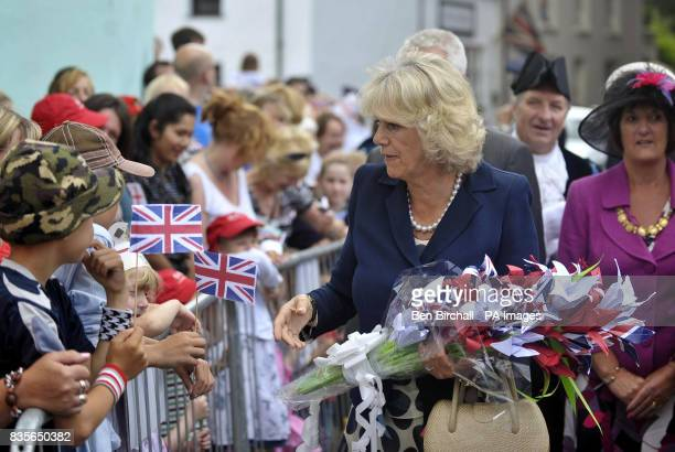 The Duchess of Cornwall receives a bunch of flowers made from paper by schoolchildren from Lostwithiel Town School during a visit to Lostwithiel...
