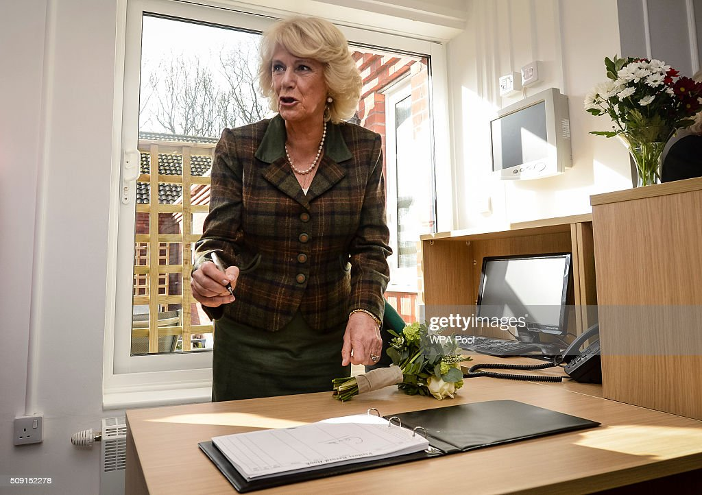 The Duchess of Cornwall signs the visitors book during a visit to Prospect Hospice's new facility at Savernake Hospital which gives care and support to patients, carers and families dealing with terminal illness on February 9, 2016 in Marlborough, England.