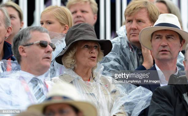 The Duchess of Cornwall wears a poncho as the rain falls during the Individual Eventing Jumping Final on day four of the London Olympic Games at...